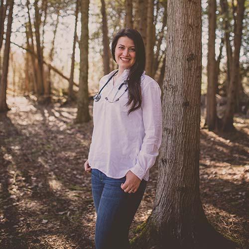 Jola Sikorski standing against a tree