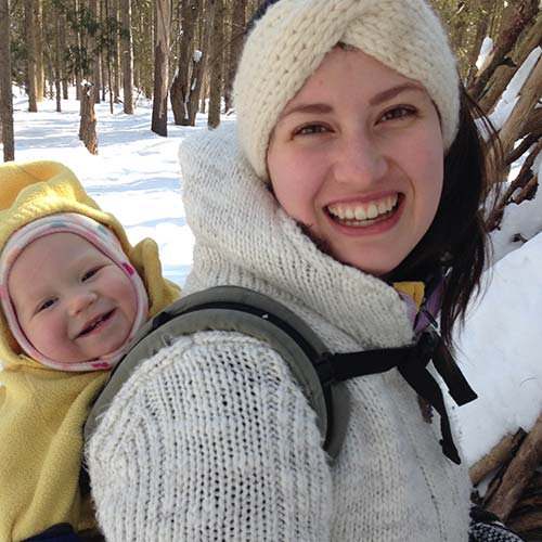 Jola Sikorski with a baby on her back, both smiling