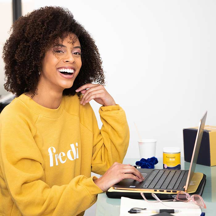 woman in yellow sweatshirt sitting in front of a laptop at a desk