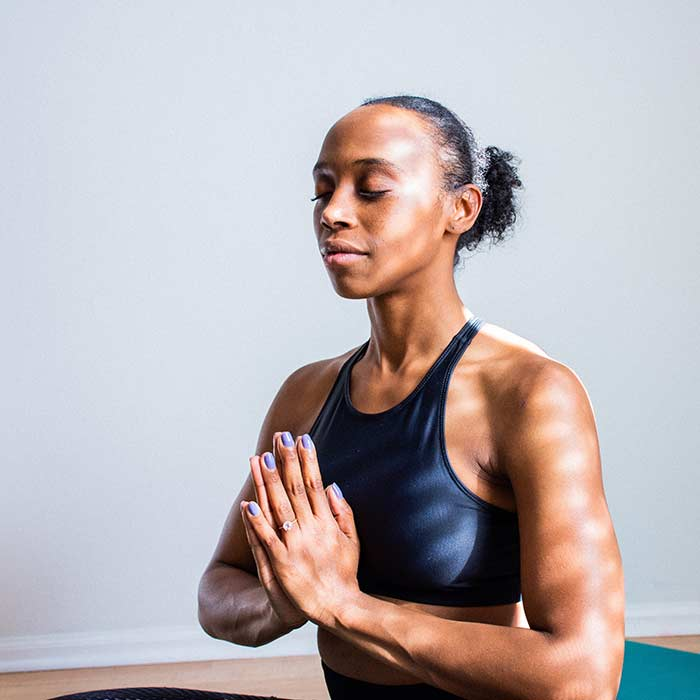 woman in blue tank-top sitting in classic meditation position