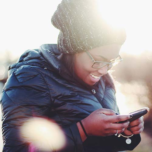 woman texting on her cellphone and smiling