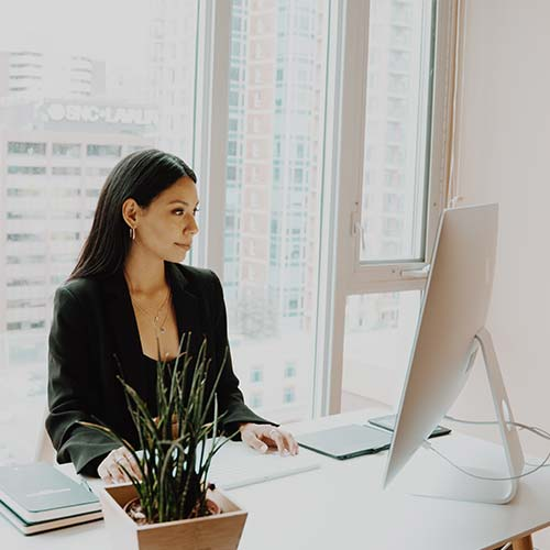 woman sitting at a desk working on a computer