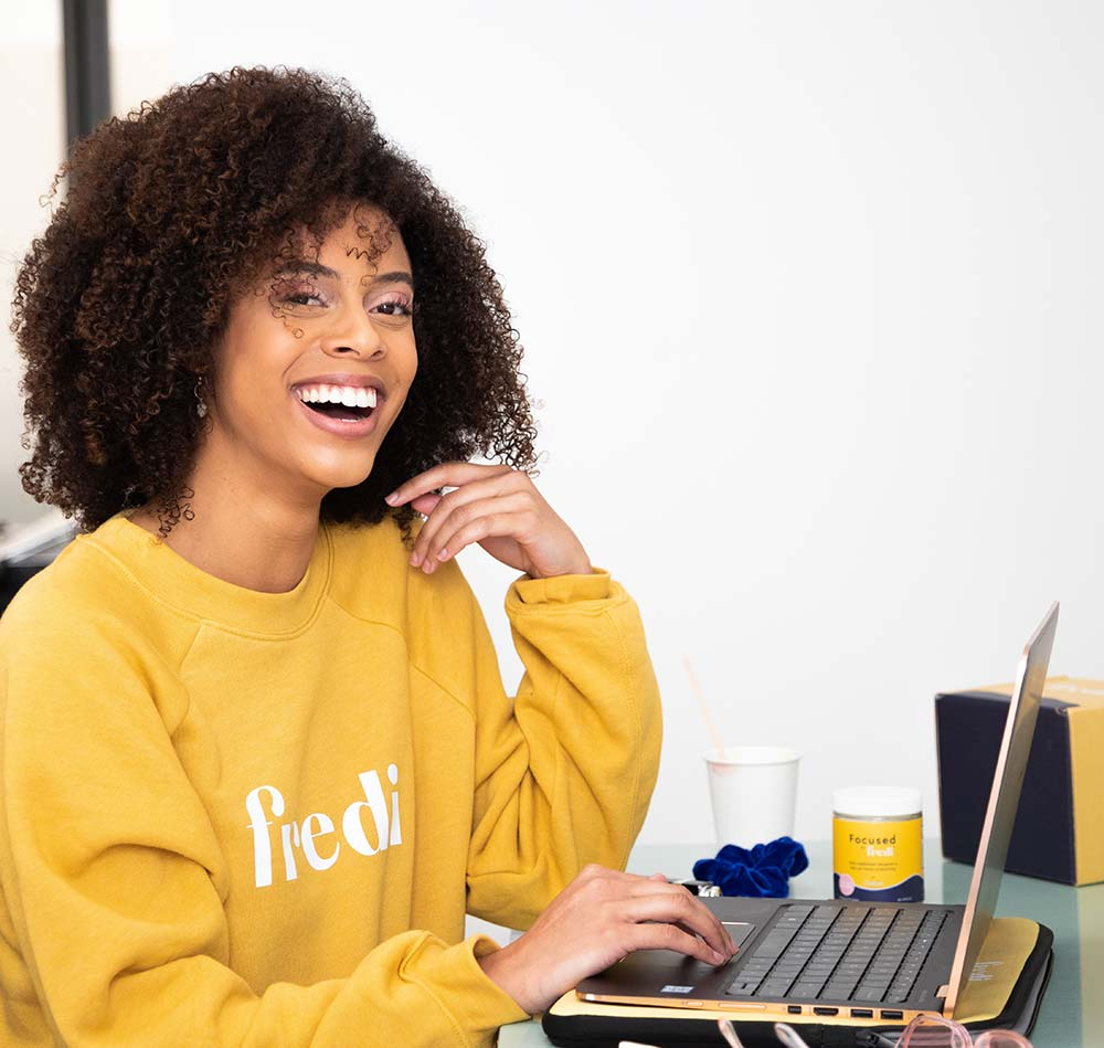 woman sitting in front of a laptop and smiling at the camera