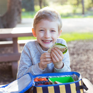 smiling young boy sitting in front of an open lunchbox and eating a sandwich
