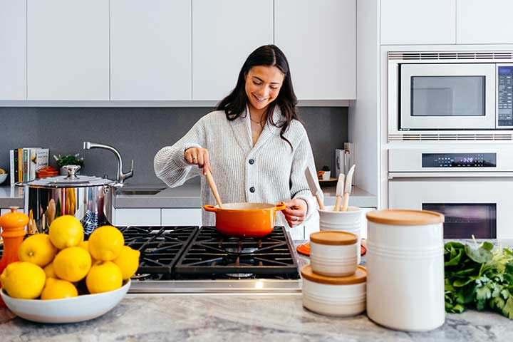 Woman stirring an orange pot with a wooden spoon over a gas hob in a modern kitchen